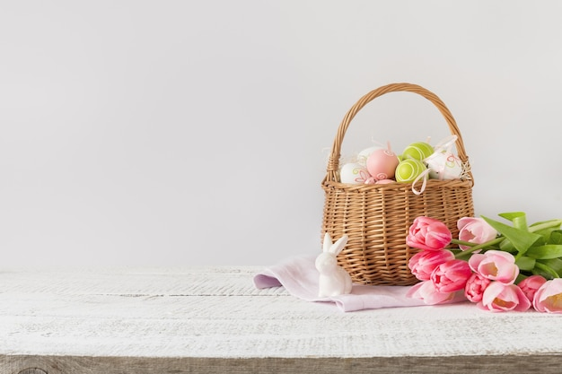 Wiklinowy kosz z pisankami i różowymi tulipanami. wiosna wielkanoc różowe tło z miejscem na tekst.