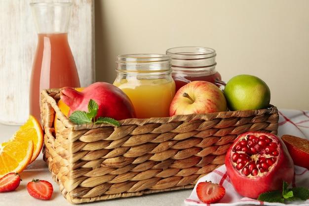 Wiklinowy kosz z różnymi sokami i owocami