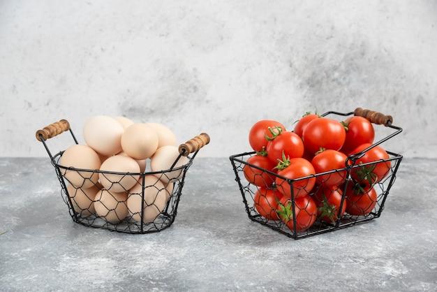 Wiklinowy kosz z surowych ekologicznych jaj i czerwonych pomidorów na marmurze.