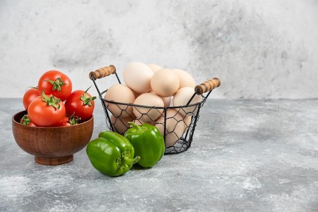 Wiklinowy kosz z surowymi organicznymi jajkami, papryką i czerwonymi pomidorami na marmurze.