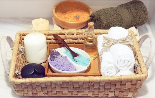 Wiklinowy kosz z zestawem do zabiegów spa, wielobarwna sól, aromatyczny olejek, kamienie, świeca i miękkie ręczniki, obok białego stołu drewniana miska z solą morską