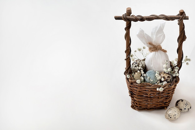 Wiklinowy koszyczek z pisanką w postaci zająca i małych nakrapianych jaj oraz białych kwiatów. wesołych świąt wielkanocnych kartkę z życzeniami, zaproszenie. miejsce na tekst