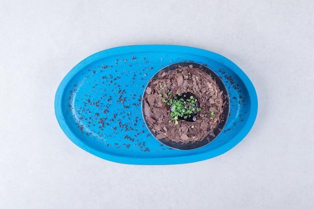 Wilgotny biszkopt czekoladowy brownie na drewnianym talerzu, na marmurze.