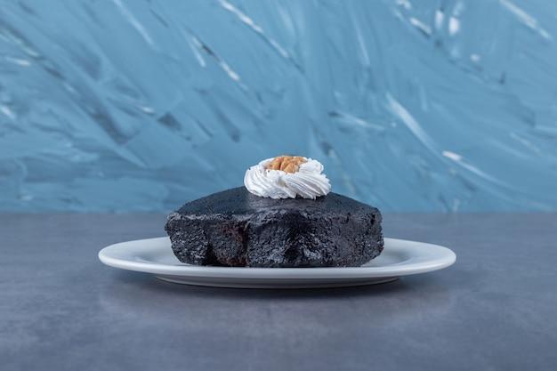 Wilgotny biszkopt czekoladowy brownie na talerzu na marmurowym stole.