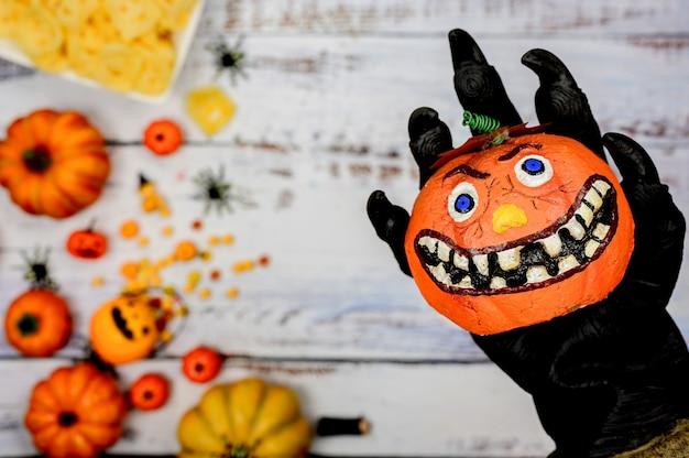 Wilk ręka trzyma twarz dyni z tłem halloween. cukierek albo psikus w sezonie jesień i jesień.