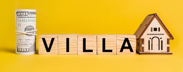 Willa z miniaturowym modelem domu i pieniędzmi na żółtym tle. pojęcie biznesu, finansów, kredytu, podatków, nieruchomości, domu, mieszkania