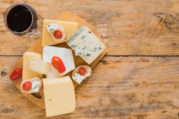 Win szkła z winogronami i rozmaitością serowi bloki na drewnianym biurku