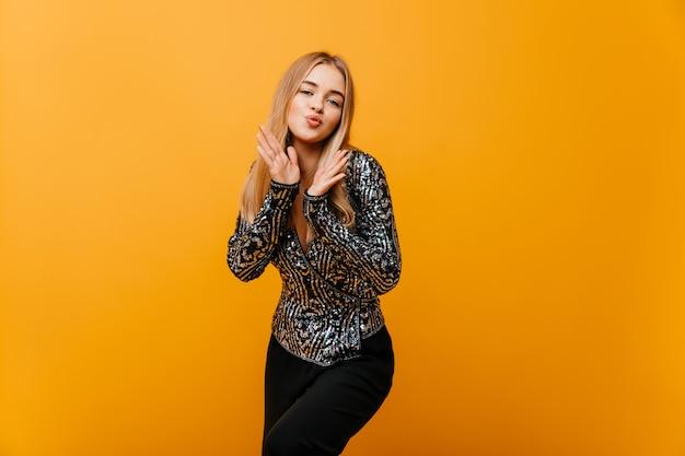 Winderful biała kobieta w stylowe ubrania taniec na pomarańczowo. zainteresowana kobieta pozuje z całowaniem twarzy expressiin.