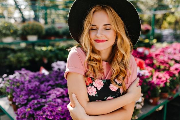 Winderful kobieta uśmiechając się z zamkniętymi oczami na oranżerii. piękna romantyczna kobieta stojąca w froncie kwiatów.