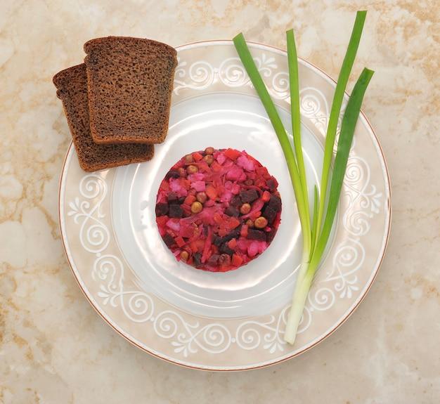 Winegret na talerzu z chlebem żytnim i zieloną cebulą