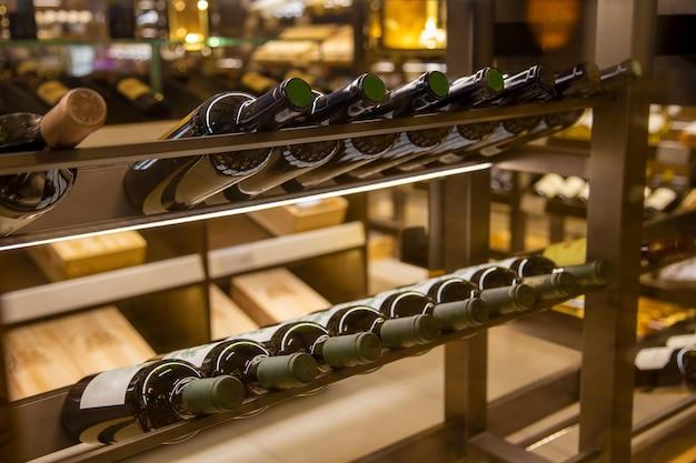 Winiarnia z elitarnymi napojami na półkach butelki wina w sklepie z bliska