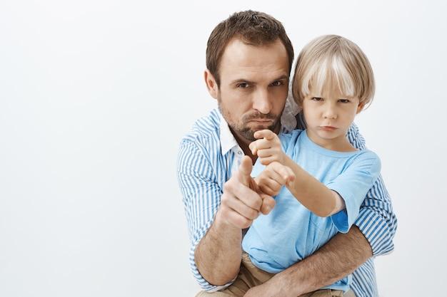 Winimy cię. portret podejrzanego niezadowolonego ojca i młodego syna z bielactwem, przytulaniem i marszczeniem brwi, mrużąc oczy, wskazując