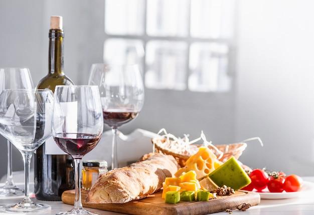 Wino, bagietka i ser na drewnianym stole