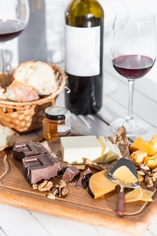 Wino, bagietka i ser na drewnianym tle