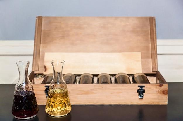 Wino białe i czerwone wlewa się do szklanego dzbanka do degustacji. w pobliżu drewnianej skrzyni z butelkami wina