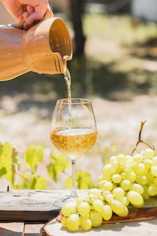 Wino bursztynowe w kieliszkach o charakterze: martwa natura z serem, winogronami i winem w stylu rustykalnym. gruzińskie wino krajowe lub włoskie wino passito
