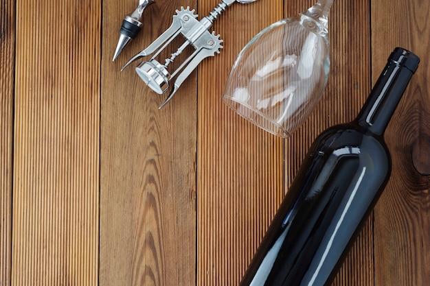 Wino butelka z wineglass corckscrew nieociosaną drewnianą deską, copyspace. leżał płasko.