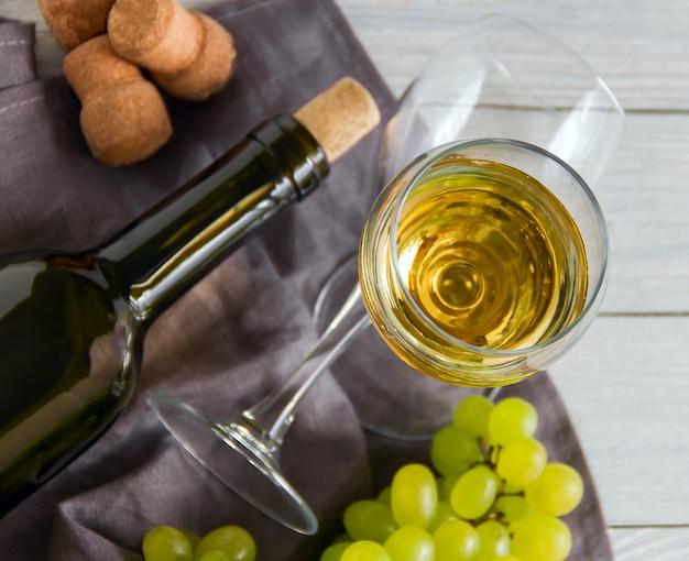 Wino butelka z winogronami na białym drewnianym stole