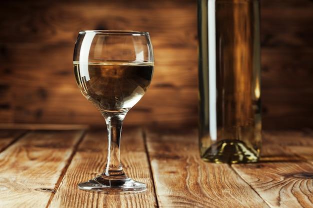 Wino butelki z szkłem, drewniany tło