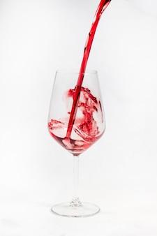 Wino czerwone przelewa się do szklanki na białym tle