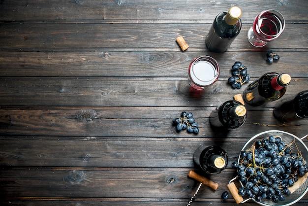 Wino. czerwone wino w okularach z winogronami. na drewnianym.
