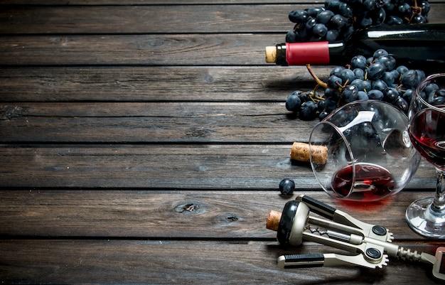 Wino. czerwone wino z korkociągiem. na drewnianym.