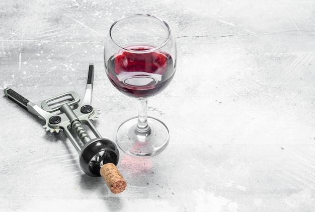 Wino. czerwone wino z korkociągiem. na rustykalnym.