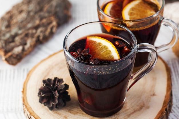 Wino grzane w kubkach z anyżem i pomarańczą na drewnianym stojaku