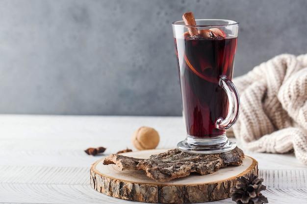 Wino grzane z laską cynamonu, przyprawy w kieliszku na drewnianym stojaku z dzianinową marynarką na wierzchu