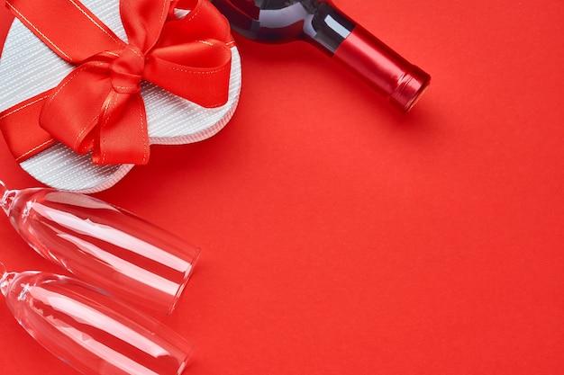 Wino, kieliszki i pudełko w formie serca z czerwoną wstążką na czerwonym tle. pocztówka koncepcja walentynki. widok z góry.