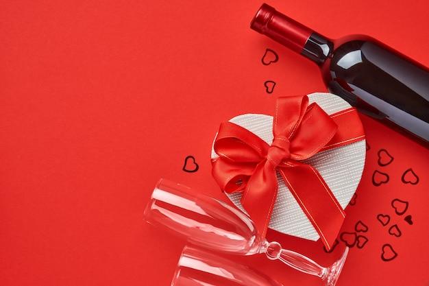 Wino, kieliszki i pudełko w formie serca z czerwoną wstążką na czerwonym tle. pocztówka koncepcja walentynki.