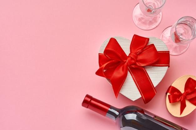 Wino, kieliszki i pudełko w formie serca z czerwoną wstążką na różowym tle. pocztówka koncepcja walentynki. widok z góry.