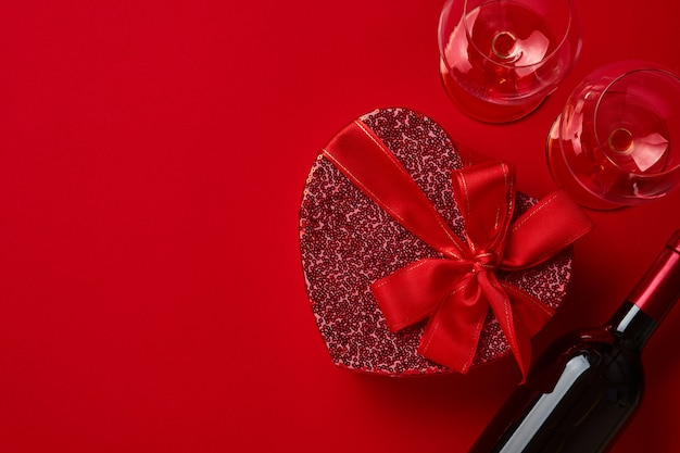 Wino, kieliszki i pudełko w formie serca z czerwoną wstążką na szkarłatnym stole. koncepcja walentynki widok z góry.