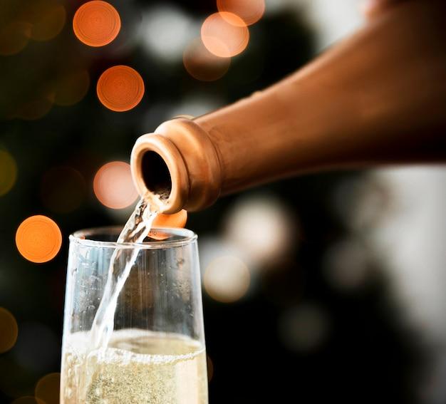 Wino musujące przelewa się w szkle na przyjęcie bożonarodzeniowe