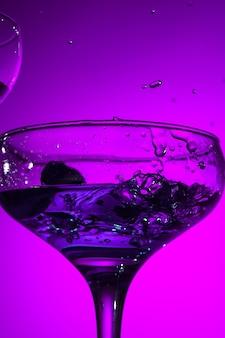 Wino nadziewane kieliszek z koktajlem stojący na stole w studio. żywe, jasne, kolorowe oświetlenie. modna w 2018 roku żarówka ultrafioletowa. dekoracja artystyczna z odcieniem mistycznego koloru