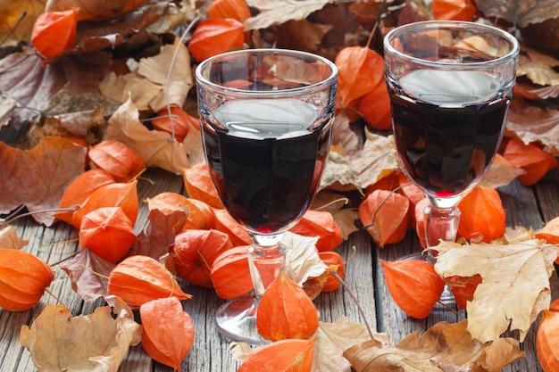 Wino przyprawione do kieliszka. czerwony liść na stole