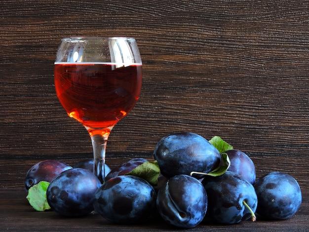 Wino śliwkowe. jasne niebieskie śliwki na ciemnym drewnianym.