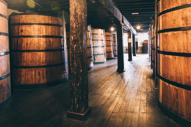 Wino w drewnianych beczkach przechowywane do starzenia w piwnicy