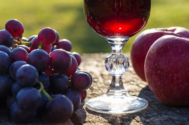 Wino w szkle i winogronach na drewnianym stole.