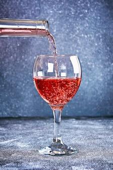 Wino w szkle. strumień wina leje się z szyjki butelki. wino na szarym tle.