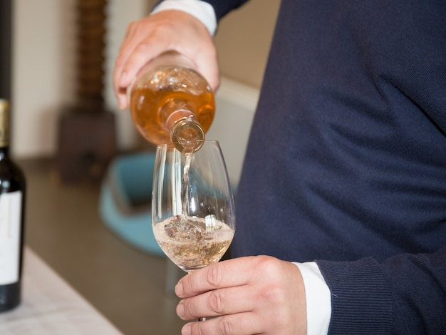 Wino wlewając do kieliszka do wina, zbliżenie