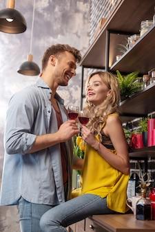 Wino z dziewczyną. kochający brodaty mężczyzna czuje się niezwykle szczęśliwy i wesoły pijąc wino ze swoją dziewczyną