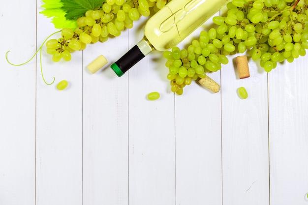Wino z gałązkami białych winogron. na drewnianym stole.