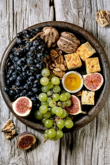 Wino z różnymi winogronami, figami, orzechami włoskimi, chlebem, miodem i kozim serem na talerzu ceramicznym na starym drewnianym tle. leżał płasko, kopia przestrzeń
