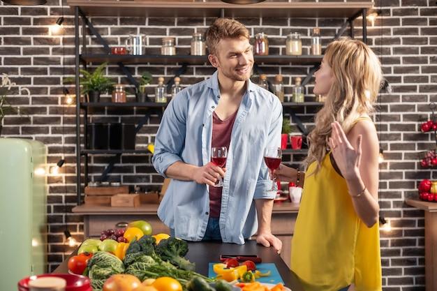 Wino z żoną. przystojny brodaty mężczyzna ubrany w niebieską koszulę, pijący wino ze swoim atrakcyjnym winem o blond włosach