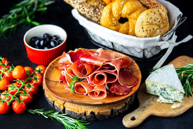 Wino zakąska na drewnianej desce. ser z białego wina, jamon, prosciutto, z salami i oliwkami na czarnym tle. świeżo upieczony chleb z przekąskami z serem i winem. smaczne przekąski imprezowe