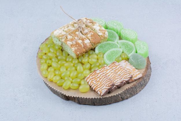 Winogrona, ciastka i marmolady na desce.