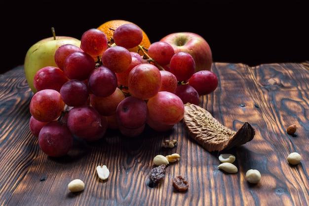 Winogrona i owoce na tle starego drewna