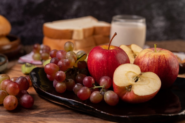 Winogrona, jabłka i chleb w talerzu na stole