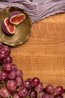 Winogrona, miedziany talerz i figi na drewnianej desce